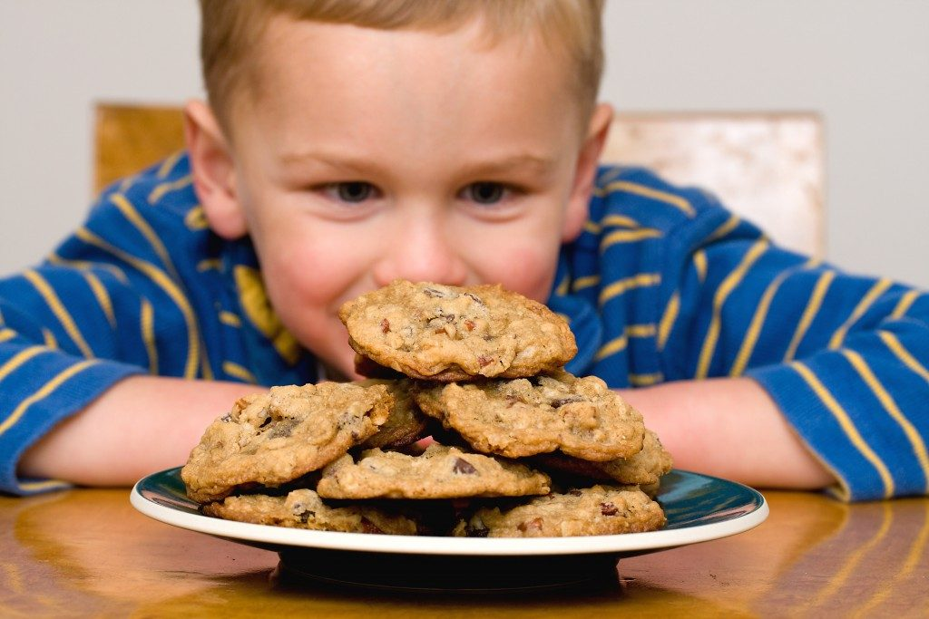 Kid looking at a plate with cookies