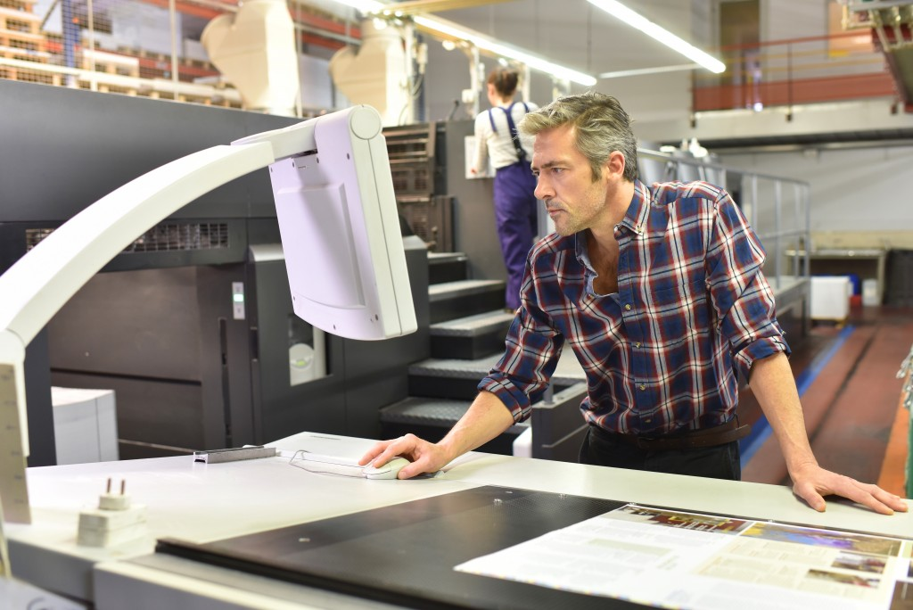 Man working with a print machine in a print factory