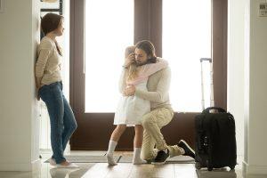 Girl hugging his leaving dad