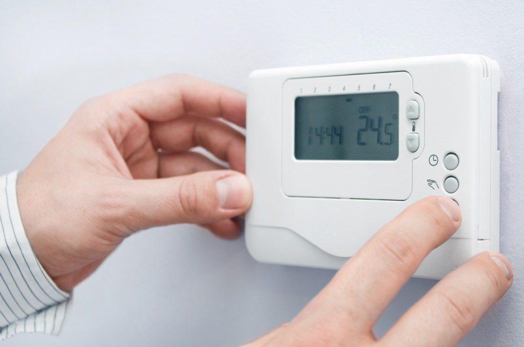 Man setting thermostat