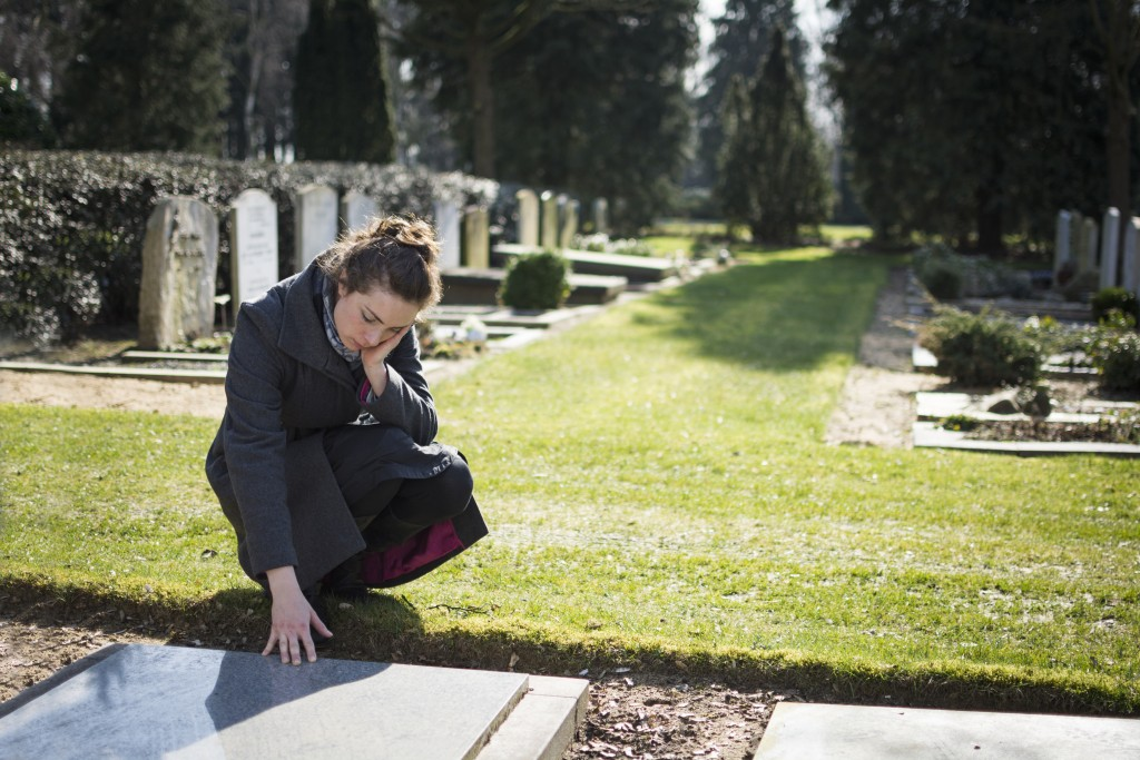 Widow grieving at the cemetery