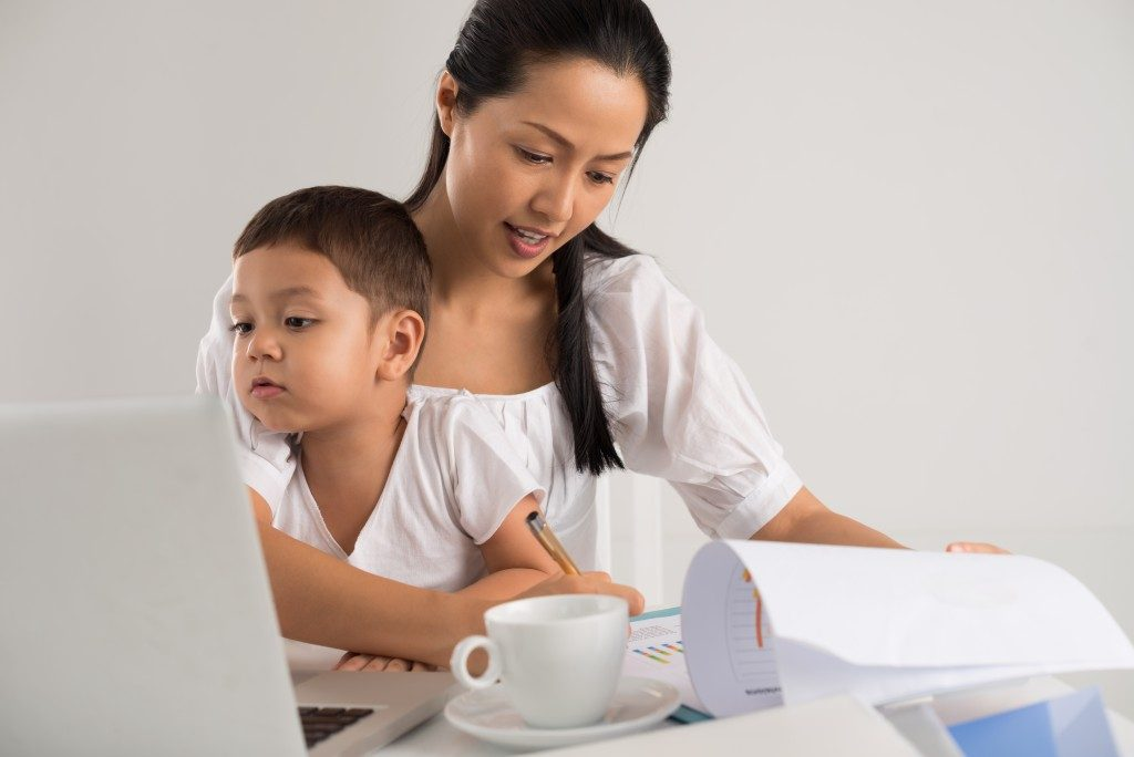 Mother working while taking care of her son
