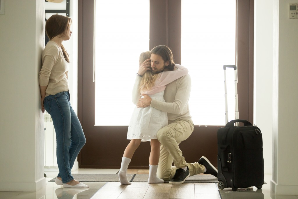 Child hugging her leaving father