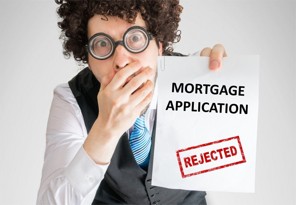 man showing paper with denied loan application
