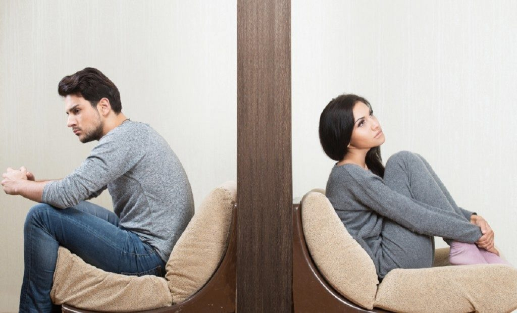 Man and woman sitting and facing the opposite direction