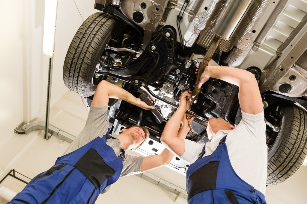 mechanics doing maintenance on car