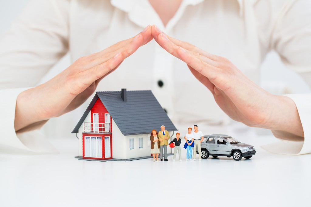 hands over tiny model of house, family and car