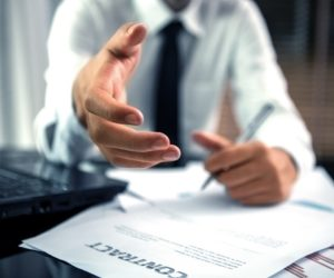 businessman extending his hand and a contract on table
