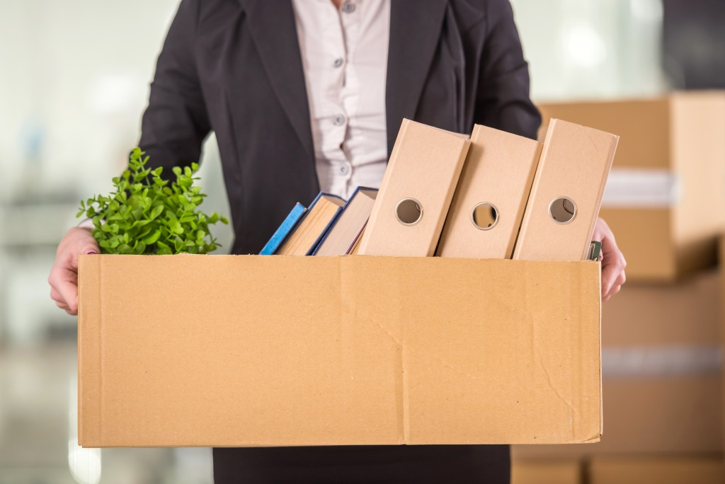 businesswoman holding cardboard box with her things