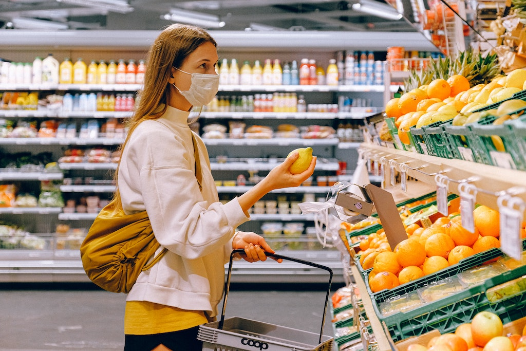 Woman buying grocery while wearing face mask