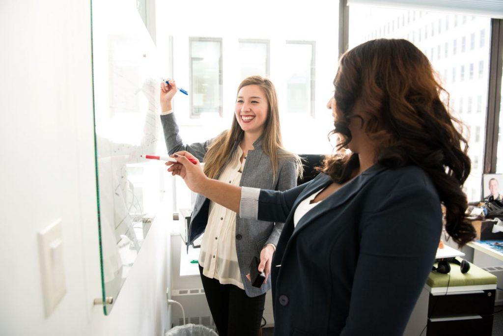 women writing on whiteboard