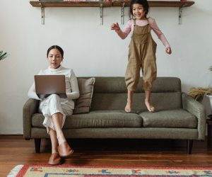 woman working with daughter jumping on couch