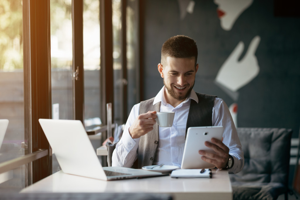 Man Holding Coffee and Tablet